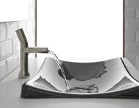 Argent robinet décoratif eau courante dans un évier décoratif gris.