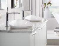 Comptoir de salle de bains avec deux lavabos décoratifs côte à côte, chacun avec un robinet argenté décoré.