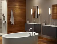 Baignoire blanche décorative circulaire au premier plan avec deux lavabos situés au-dessus des armoires de salle de bain côte à côte à l'arrière-plan.
