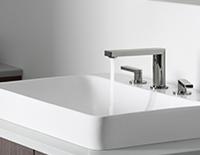 Robinet argenté décoratif qui coule dans un évier de salle de bain décoratif.
