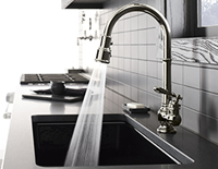Decorative faucet running water into a built-in kitchen sink with a counter-top stove in the background.
