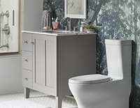 Decorative white toilet next to a grey bathroom sink cabinet unit.