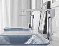 Decorative bathroom glass sinks with silver faucet and the same sink in the background.
