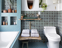 Decorative green glass sink with a brown countertop over a shelf of stacked towels next to a decorative toilet and bathtub.
