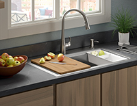 Decorative built-in kitchen sink with a silver faucet that has a cutting board over half the sink.