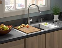 Évier de cuisine décoratif encastré avec un robinet en argent muni d'une planche à découper sur la moitié de l'évier.